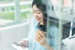 retrato, de, feliz, joven, mujer de negocios, utilizar, ella, teléfono, por la puerta de vidrio foto