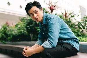 Joven apuesto asiático en el fondo del jardín verde foto