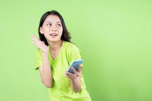 Image of young asian woman holding smartphone on green background photo