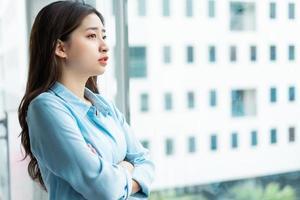Retrato de una joven empresaria asiática con los brazos cruzados y pensando junto a la ventana foto