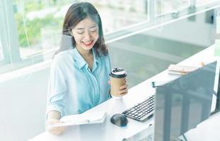 Retrato de joven empresaria asiática en el trabajo foto