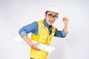 Sonriente joven ingeniero civil asiático con casco casco de pie sobre fondo blanco aislado. concepto de servicio mecánico. foto