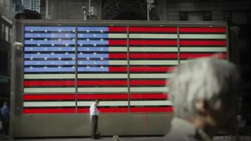 A man stands in front of an electronic representation of the American flag video