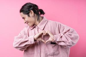 Long haired young Asian man, wearing pink shirt, smiling on pink background photo