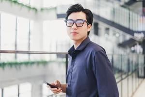 Portrait of an Asian businessman, confident and smiling, holding a phone in his hand photo