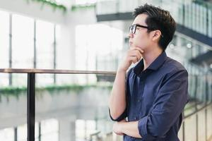 Young Asian business guy standing thinking photo