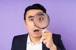 Business man in suit wearing magnifying glass, isolated on purple background photo