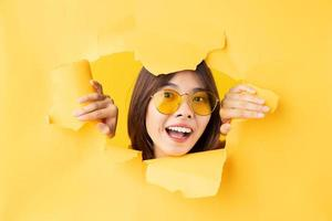 joven asiática asomó la cabeza a través del papel rasgado foto