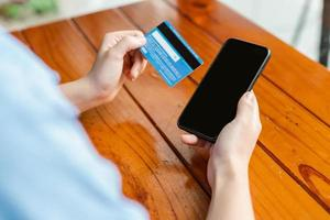 Woman's hand holding payment card and using smartphone photo