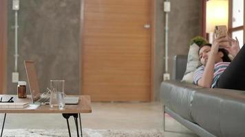 belle jeune femme asiatique travaillant à la maison pendant la quarantaine allongée à l'aide d'un téléphone portable dans le salon en attendant un appel de chat sur ordinateur portable sur une commande de commerce électronique sur Internet, une entreprise d'achat en ligne. video