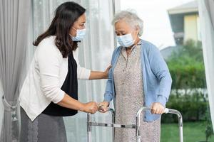Help and care Asian senior or elderly old lady woman use walker with strong health while walking in hospital. photo