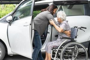 Help and support asian senior or elderly old lady woman patient sitting on wheelchair prepare get to her car, healthy strong medical concept. photo
