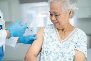 Elderly Asian senior woman wearing face mask getting covid-19 or coronavirus vaccine by doctor make injection. photo