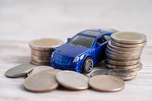 Car on stack of coins. Car loan, Finance, saving money, insurance and leasing time concepts. photo