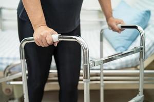 paciente asiática dama dolor de espalda, cintura, pierna y lumbar ortopédico con andador. foto