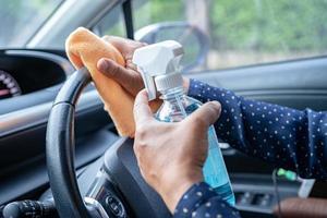 nueva mujer trabajadora asiática normal limpia en el automóvil presionando gel desinfectante de alcohol azul para proteger la seguridad del coronavirus. foto