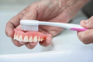 Asian senior or elderly old woman patient use toothbrush to clean partial denture of replacement teeth. photo