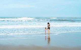 vacaciones, mamá e hija en la playa, arena, sostiene la mano foto