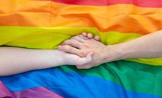imagen de una pareja gay cogidos de la mano en la bandera lgbt foto