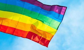 imagen de la bandera lgbt ondeando en el cielo azul foto
