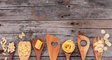Italian foods concept and menu design . Various kind of pasta elbow macaroni, farfalle ,rigatoni ,gnocco sardo in wooden spoons setup on wooden background photo