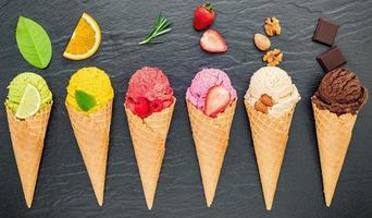 Varios sabores de helado en conos de arándano, lima, pistacho, almendra, naranja, chocolate, vainilla y café sobre fondo de piedra oscura. concepto de menú de verano y dulces foto