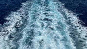 Perspective of a person sailing on a big ship and cruising across the vast blue sea as it creates ripples and waves on the deep waters, tracking backwards video