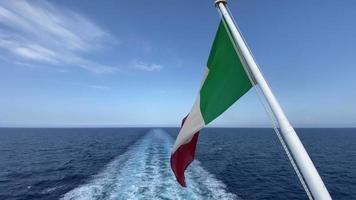 A flag of Italy with the civil ensign gently waving with the wind as a boat sails in slow motion across the vast blue sea during a sunny day. video
