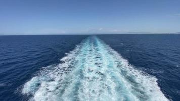 An astounding scenery of the wide blue ocean viewed from a big boat sailing and creating waves and splashes on the surface during a bright sunny day, tracking backwards. video