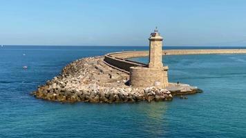 vue aérienne d'un phare haut et robuste avec des rochers au bord d'un long port sinueux au milieu de la grande mer bleue pendant une journée ensoleillée, tournant lentement vers la droite. video