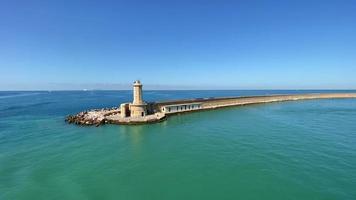 un beau paysage d'un phare au bout d'un long port avec des côtes rocheuses situé au milieu de la mer vaste et douce pendant la journée, lentement panoramique vers la droite. video