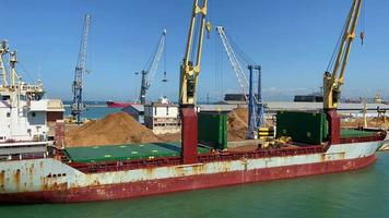 Aerial angle of a tractor going back and forth in a particular area of a big ship as it levels piles of soil on the port nearby the wide sea during daytime. video