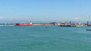A bright sunny day on the harbor with ships carrying several cargoes to deliver to other ports and sail on the wide blue sea, wide view slowly panning to the right. video