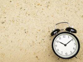 Despertador en la arena de la playa, mostrando las diez en punto. foto