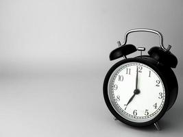 Despertador aislado en blanco, en negro con sombra, mostrando las siete foto
