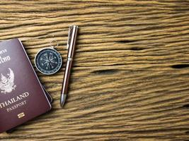 Planning travel concept, Thailand passport and pen on wooden background photo