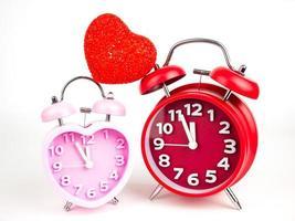 Despertador rojo y rosa en forma de corazón aislado sobre fondo blanco, el día de San Valentín foto