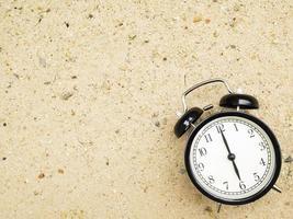 Despertador en la arena de la playa, mostrando las seis en punto. foto