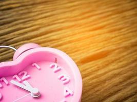 Despertador rosa en forma de corazón sobre fondo de madera foto