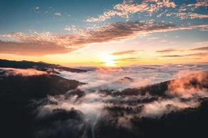 The sun rises in the mist and mountains in the morning photo