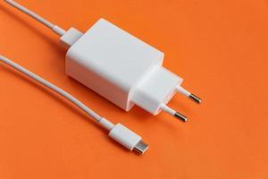 Cargador y cable usb tipo c sobre fondo naranja foto