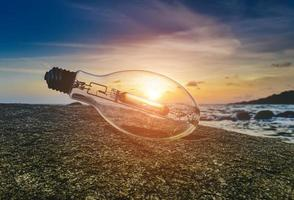 Light bulb trash on the beach with sunlight. photo