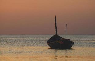 Fishery wooden boat with sunset sky low lighting. photo