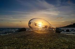 Basura de bombilla en la playa con luz solar. foto
