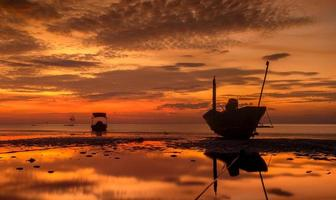 Silhouette Fishery wooden boat with sunset sky low lighting. photo
