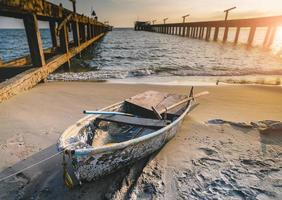 Small fishery wooden boat on the beach. photo