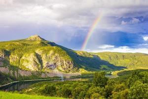 colorido arco iris sobre el lago vangsmjose y el panorama de la montaña noruega. foto