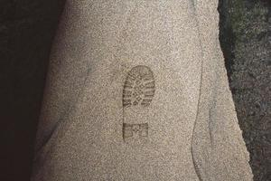 Imprint of shoe on mud with copy space. Foot step on sand photo