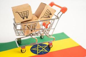 caja con el logotipo del carrito de compras y la bandera de Etiopía, importación, exportación, compras en línea o comercio electrónico, servicio de entrega de finanzas, tienda, envío de productos, comercio, concepto de proveedor. foto
