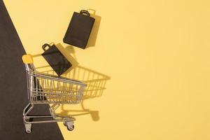Carro de supermercado en miniatura laicos plana con bolsas de la compra en venta de viernes negro sobre fondo amarillo foto